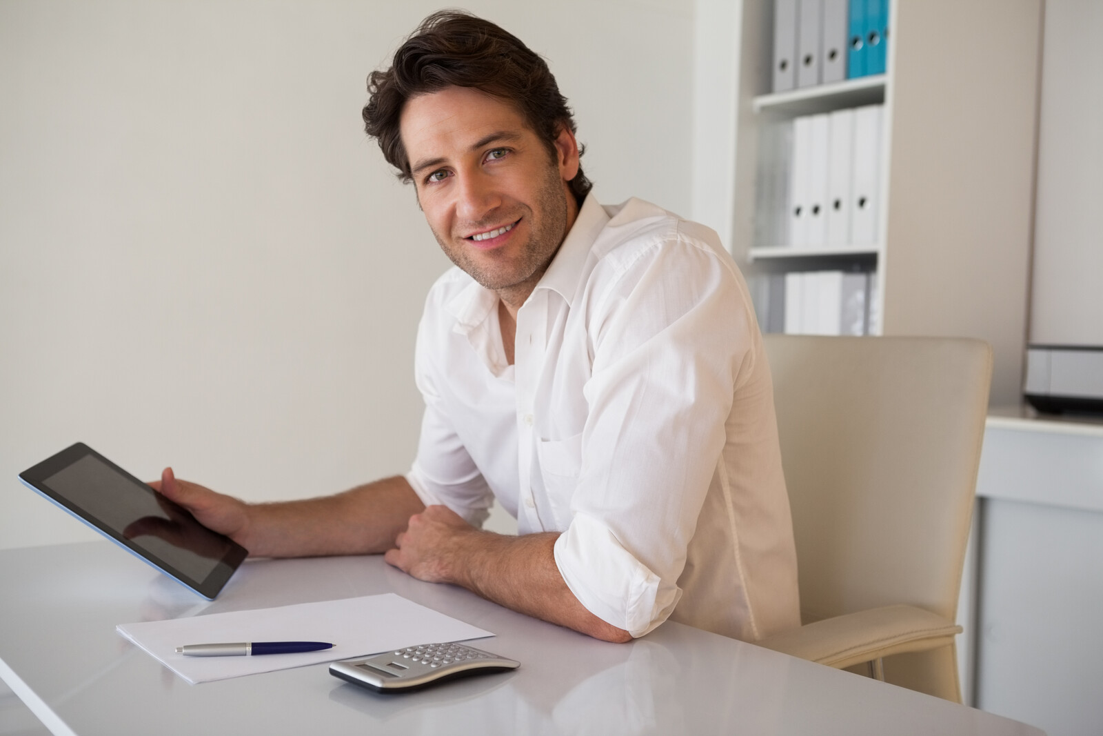 A man smiling while using his Ipad