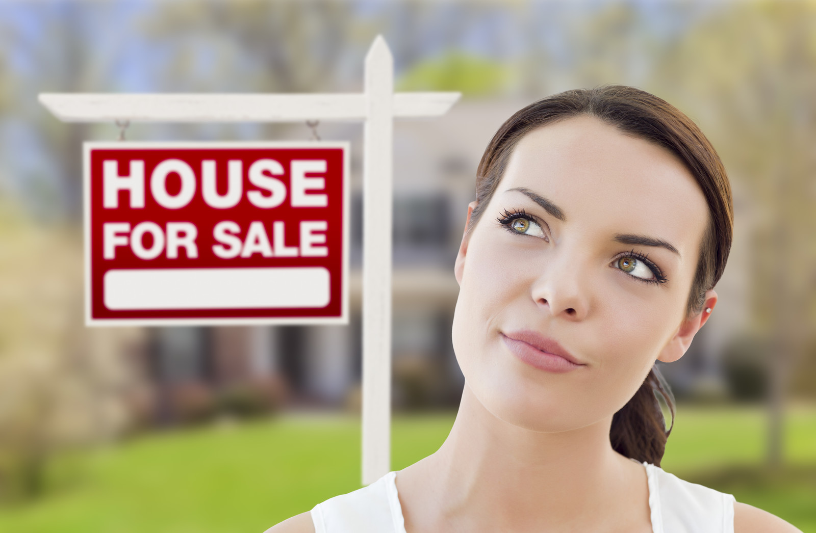 "A woman looking off into the distance, next to a ""House For Sale"" sign"