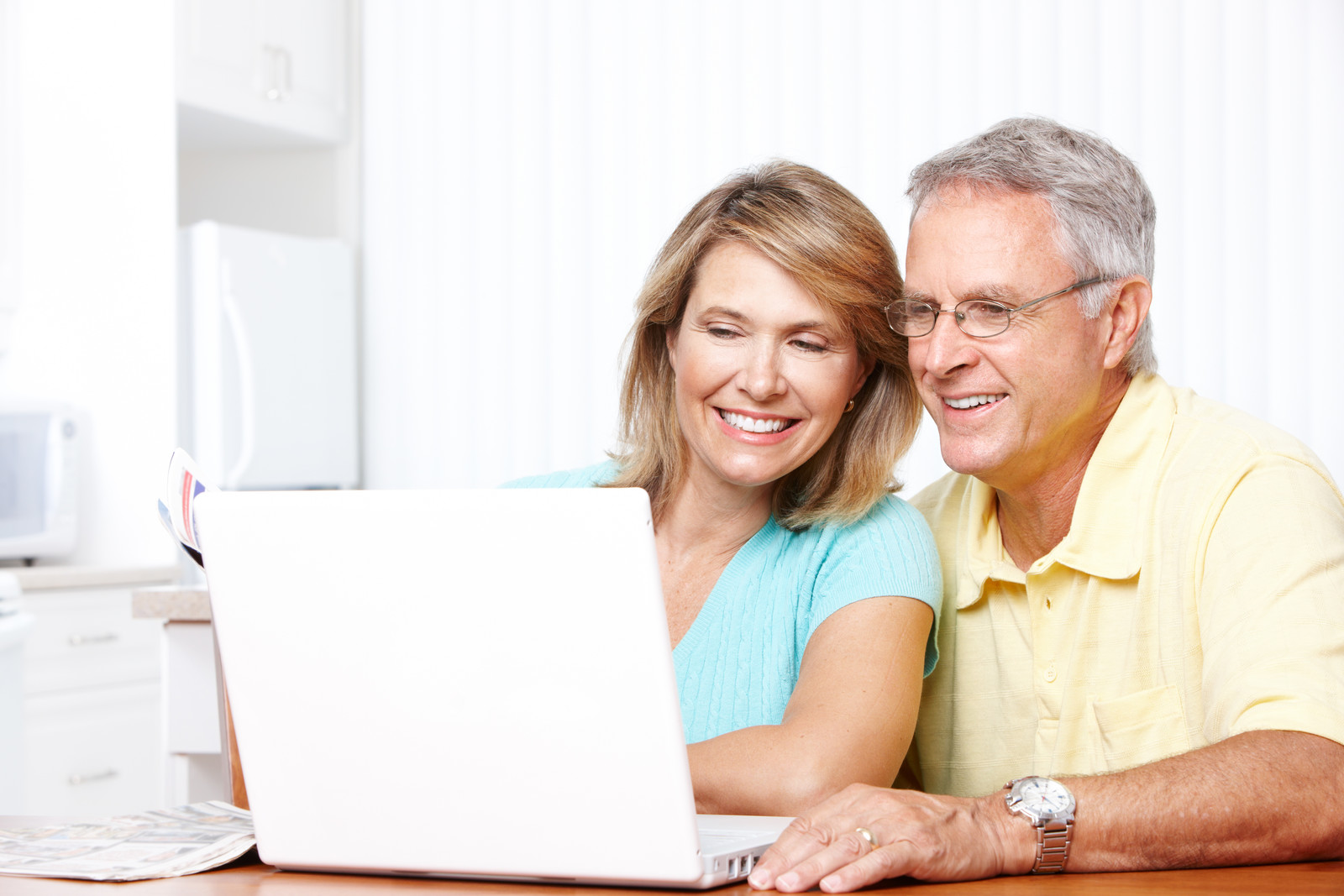Middle aged couple smiling while looking at computer