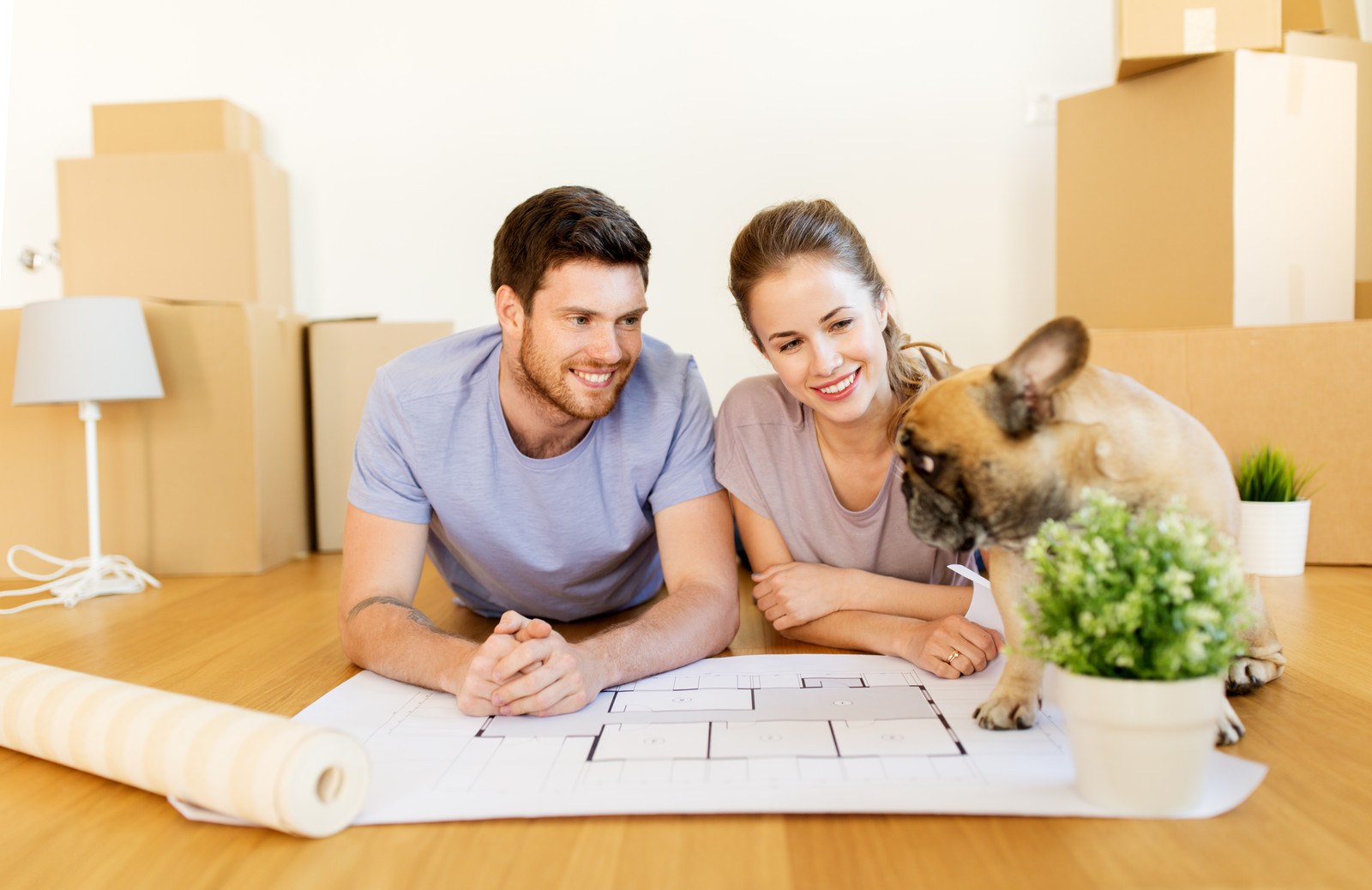 A man and women smiling at their dog while they work on their plans for a new home