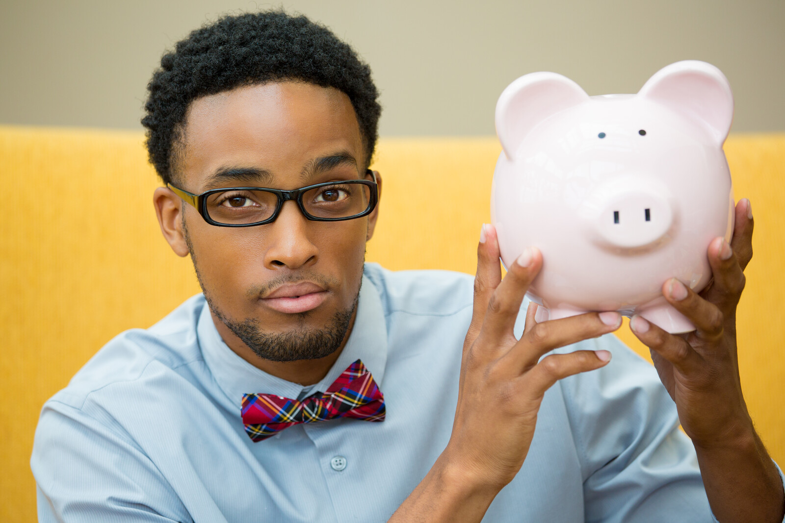A man with glasses holding up a piggy bank