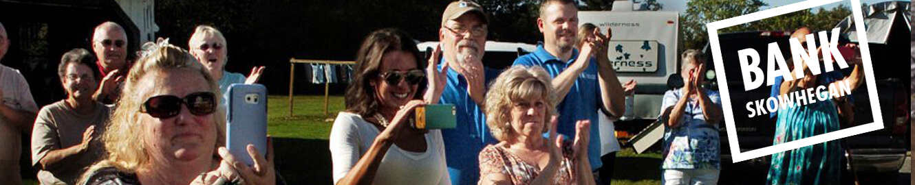 "A group of people taking pictures with their smartphones, with the text ""Bank Skowhegan"""